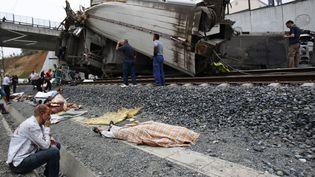 Un passager blessé est assis près du corps d'une des victimes du train qui a déraillé près de Saint-Jacques-de-Compostelle (Espagne), le 24 juillet 2013 (MONICA FERREIROS / LA VOZ DE GALICIA)