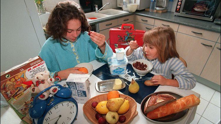 Deux enfants prennent leur petit-déjeuner. (Photo d'illustration) (MYCHELE DANIAU / AFP)
