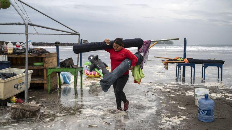 Une femme retire les parasols d'une plage alors que l'ouragan Grace se rapproche de la côte nord de Veracruz (Mexique), le 20 août 2021. (VICTORIA RAZO / AFP)
