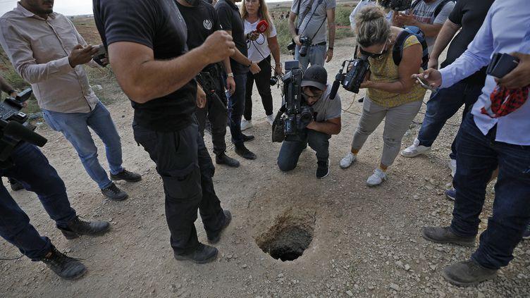Des policiers et journalistes rassemblés autour du trou par lequel les détenus palestiniens se sont évadés de la prison de Gilboa (Israël), le 6 septembre 2021. (JALAA MAREY / AFP)