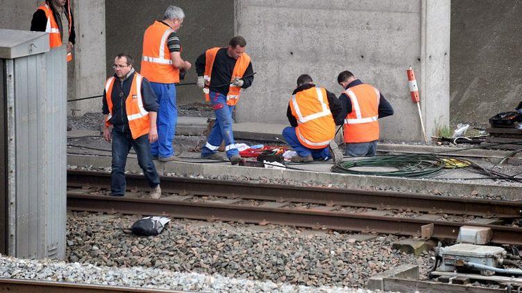 Des employés de la SNCF travaillent sur des rails de TGV le 26 avril 2011, après un vol de câbles en cuivre dans la nuit. (PHILIPPE HUGUEN / AFP)