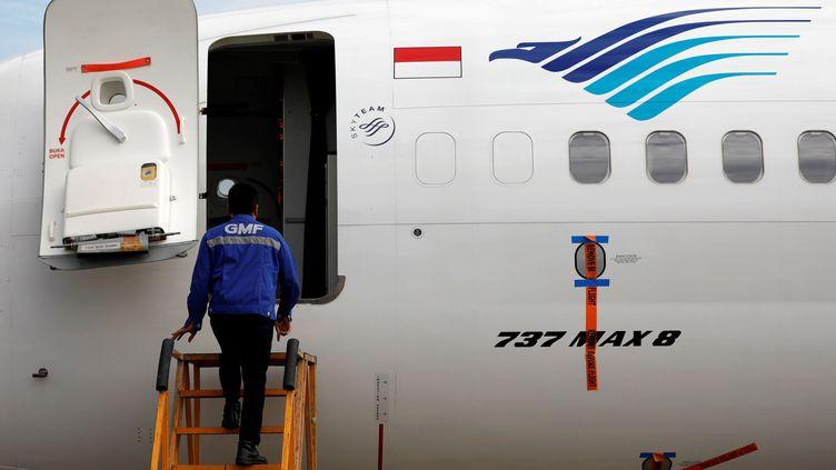 Un technicien monte à bord d'un Boeing 737 Max 8, àJakarta (Indonésie), le 13 mars 2019. (WILLY KURNIAWAN / REUTERS)