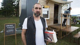 Jean-Jacques Megel-Nuber, libraire itinérant an Alsace, devant sa librairie ambulante  (PATRICK HERTZOG / AFP)