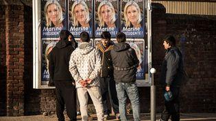 Des migrants devant des affiches de campagne de Marine Le Pen, tête de liste FN en Nord-Pas-de-Calais-Picardie, le 7 décembre2015 à Calais. (PHILIPPE HUGUEN / AFP)
