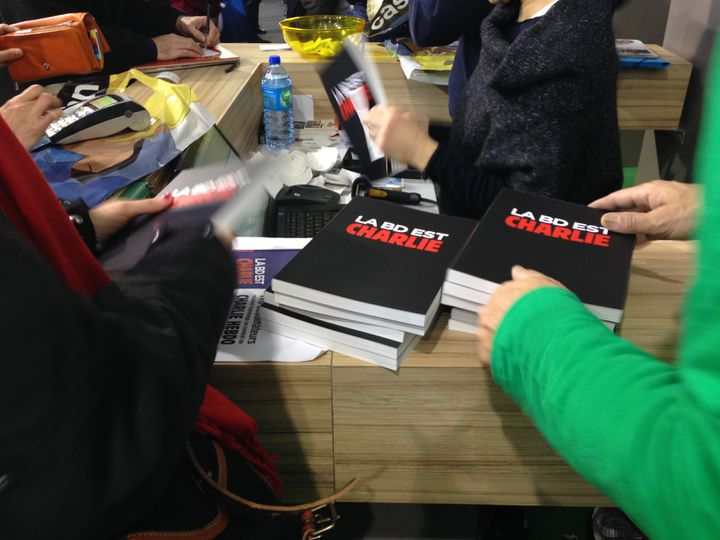 """Aux caisses, presque tout le monde prend son exemplaire de """"La BD est Charlie"""", le 31 janvier 2015, lors du festival de la BD d'Angoulême. (JULIE RASPLUS / FRANCETV INFO)"""