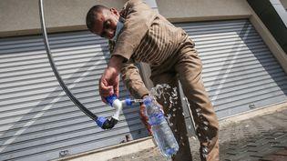 Un Palestinien remplit une bouteille d'un générateur d'eau alimenté par l'énergie solaire, dans la ville de Khan Yunisà Gaza, le 16 novembre 2020. (SAID KHATIB / AFP)