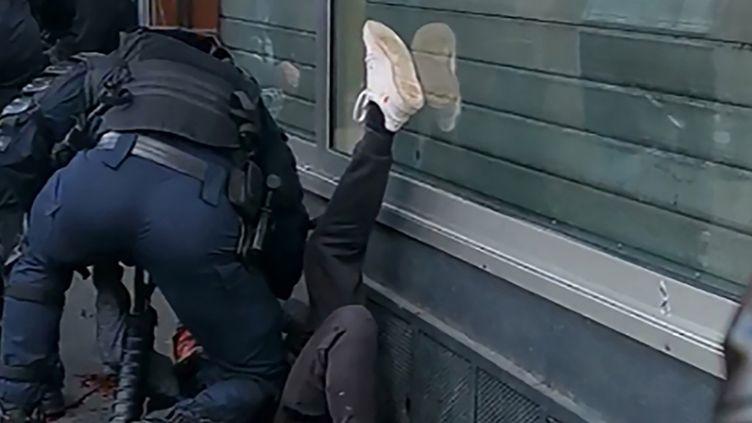 Capture écran de la vidéo où un policier frappe un manifestant au sol. (- / HANDOUT)