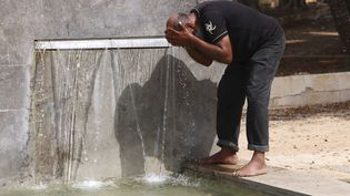 Un homme se rafraîchitdans une fontaine de Palerme, en Sicile (Italie), le 11 août 2021. (ALBERTO LO BIANCO / LAPRESSE / AFP)