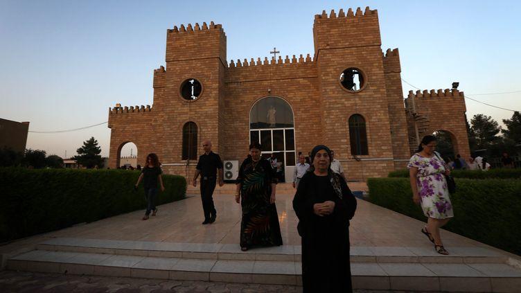 Des chrétiens irakienssortent de la messe, le 20 juillet 2014, à Arbil, capitale de la région autonome du Kurdistan, où ils ont trouvé refuge. (SAFIN HAMED / AFP)