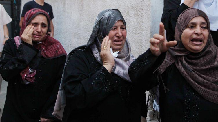 Des femmes pleurent des victimes palestiniennes de l'offensive israélienne, à Gaza, le 18 juillet 2014. (ASHRAF AMRA / ANADOLU AGENCY / AFP)