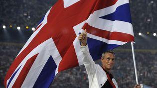 Le nageur britannique Mark Foster porte le drapeau de la Grande-Bretagne lors de la cérémonie d'ouverture des JO de Pékin (Chine), le 8 août 2008. (JEWEL SAMAD / AFP)