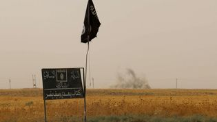 De la fumée s'élève en arrière-plan d'un drapeau de l'organisation Etat islamique, dans la province de Dakouk, au sud de Kirkouk, en Irak, le 11 septembre 2015. (MARWAN IBRAHIM / AFP)