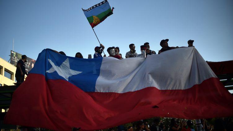 Des manifestants tiennent un drapeau chilien, le 12 novembre 2019, à Santiago (Chili). (RODRIGO ARANGUA / AFP)