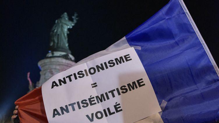 """Lors du rassemblement contre l'antisémitisme place de la République à Paris, le 19 février 2019, un homme brandit un drapeau français sur lequel on peut lire """"Antisionisme = antisémitisme voilé"""". (ANTONI LALLICAN / HANS LUCAS / AFP)"""