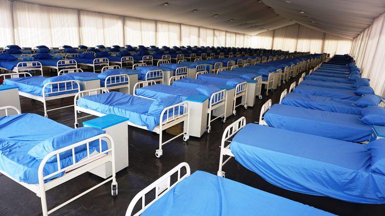 En soutien aux hôpitaux de l'Etat de Kano (nord du Nigeria) qui manquent de moyens, des centaines de lits ont été installés sous une tente dans un stade, grâce à un don de l'homme d'affaires nigérian Aliko Dangote (photo prise le 7 avril 2020). (AMINU ABUBAKAR / AFP)