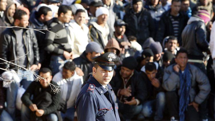 Un policier italien devant des migrants arrivés de Tunisie sur l'île de Lampedusa le 13 février 2011. (REUTERS/Antonio Parrinello)