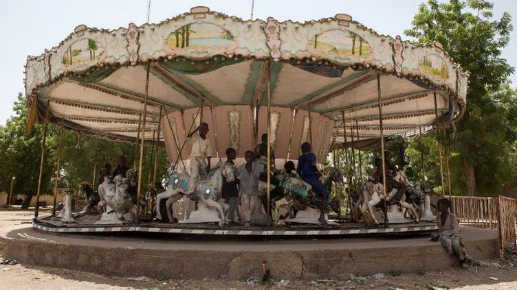 Rendus orphelins par les attaques de Boko Haram, des enfants nigérians s'amusent avec le manège d'un parc d'attraction abandonné de Maiduguri, le 27 avril 2017. Depuis l'apparition du groupe djihadiste, la population de cette ville a doublé, passant à deux millions de personnes, dont des milliers d'enfants sans domicile. (Florian PLAUCHEUR / AFP)