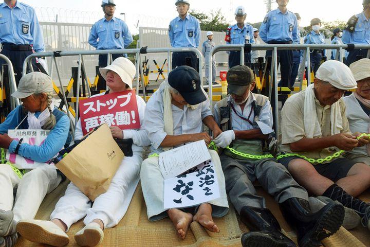 Des manifestants antinucléaires manifestent contre le redémarrage de la centrale de Sendai (Japon), le 11 août 2015. (JIJI PRESS / AFP)