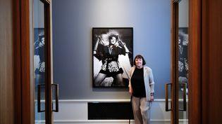 """La photographe June Newton ou Alice Springs pose à côté d'un de ses clichés représentant son mari Helmut Newton à l'exposition """"Alice Springs"""" en juin 2010 à Berlin. (JOHANNES EISELE / AFP)"""