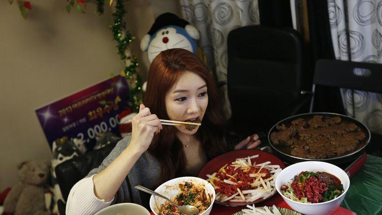 Park Seo-yeon, une Sud-Coréenne de34 ans, mange devant son ordinateur, à Séoul (Corée du Sud), le 22 janvier 2014. (KIM HONG-JI / REUTERS)