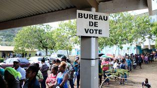 Des électeurs font la queue pour voter devant un bureau de vote à Nouméa, en Nouvelle-Calédonie, le 4 octobre 2020. (THEO ROUBY / AFP)