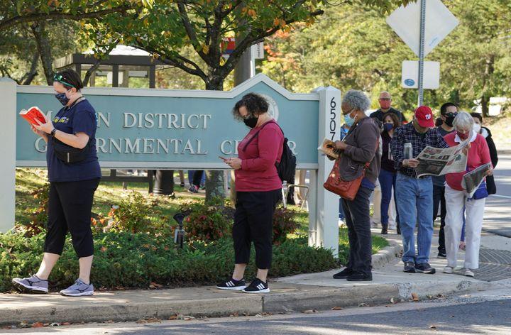 Les électeurs font la queue pour accéder aux bureaux de vote, comme à Annandale (Virginie), le 14 octobre 2020. (KEVIN LAMARQUE / REUTERS)