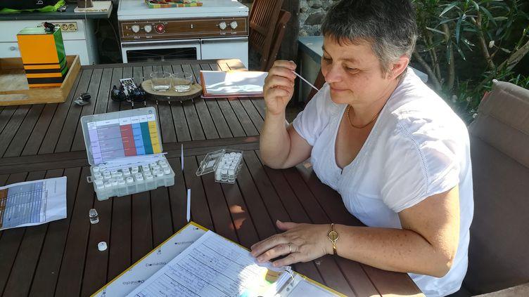 Chrystèle Alviset s'entraîne à identifier une odeur imprégnée sur une languette de papier, le 10 juillet 2018, à son domicile, dans le bassin de Lacq (Pyrénées-Atlantiques). (HUGO CAILLOUX / FRANCEINFO)