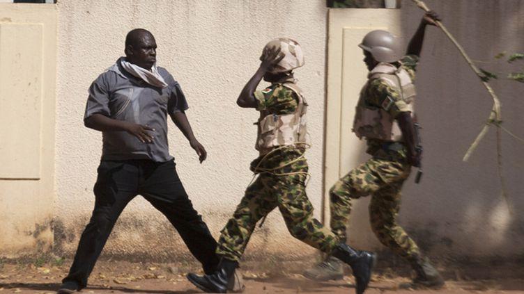 (Des soldats frappent un opposant au président Compaoré ce jeudi au Burkina Faso. © REUTERS/Joe Penney)