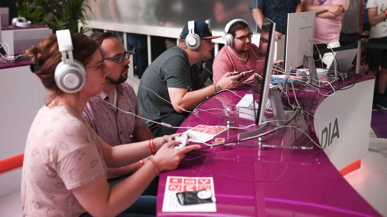 """Au """"Gamescom"""" de Cologne (Allemagne), des visiteurs jouent avec le cloud gaming """"Doom"""" dans le stand de Google Stadia, le 21 août 2019. (INA FASSBENDER / AFP)"""