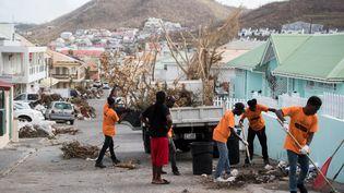 Des habitants de Saint-Martin nettoient les rues de Marigot, le 12 septembre 2017, après le passage de l'ouragan Irma sur l'île. (MARTIN BUREAU / AFP)