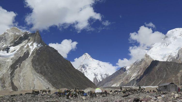 Des porteurs montent des tentes au camping de Concordia devant le sommet du K2 (au centre), dans la chaîne du Karakoram, au nord du Pakistan, le14 août 2019. (AMELIE HERENSTEIN / AFP)