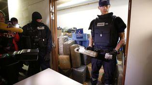 Des officiers des douanes devant le contenu d'une importante saisie de résine de cannabis, ausiège de la douane à Ivry-sur-Seine (Val-de-Marne), dimanche 18 octobre. (PIERRE CONSTANT / AFP)