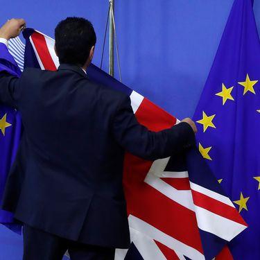 Un employé de la Commission européenne met en place des drapeaux avant une session de négociations sur le Brexit à Bruxelles, le 17 juillet 2017. (YVES HERMAN / REUTERS)