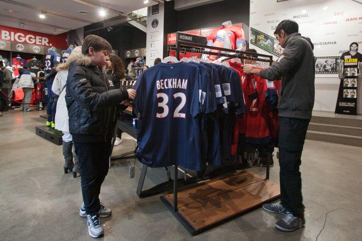 Des supporters du PSG s'intéressent au maillot de David Beckham dans la boutique du club, le 1er février 2013. Le joueur anglais devrait toucher un pourcentage sur chaque maillot vendu. (MARC PIASECKI / GETTY IMAGES)