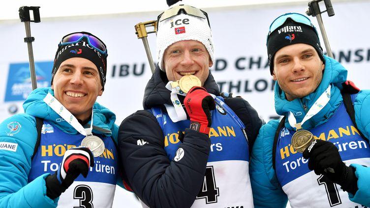 Le double tenant du titre de la Coupe du monde de biathlon, le Norvégien Johannes Boe, entouré ici des Français Quentin Fillon Maillet (à gauche) et Émilien Jacquelin (à droite). (MARCO BERTORELLO / AFP)