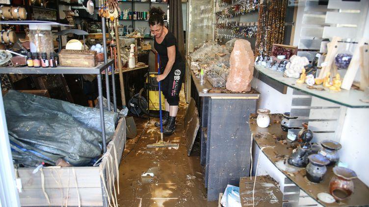Une commerçante nettoie son magasin, à Ajaccio (Corse-du-Sud), après les intempéries, le 12 juin 2020. (PASCAL POCHARD-CASABIANCA / AFP)
