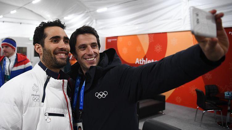 Le champion olympique de biathlon Martin Fourcade et Tony Estanguet, le président du Comité d'organisation des JO de Paris, à Pyeongchang, le 19 février. (FRANCK FIFE / AFP)