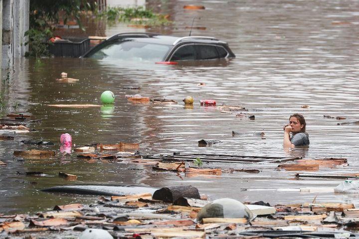 Une personne dans une rue inondée de Liège en Belgique, le 15 juillet 2021. (BRUNO FAHY / BELGA MAG / AFP)