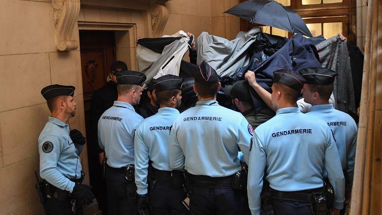 Des gendarmes encadrent les prévenus qui se protègent des caméras et des appareils photo par des parapluies et des blousons, le 20 septembre 2017, à Paris. (ERIC FEFERBERG / AFP)
