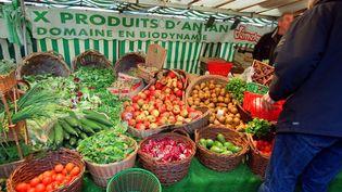 Une personne choisit des légumes provenant de la culture biologique, le 19 novembre 2000 dans un marché de Paris. (JEAN-PIERRE MULLER / AFP)