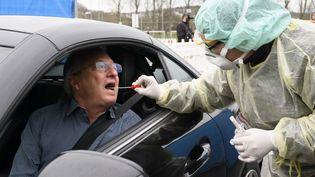 """En Allemagne, des points de tests au Covid-19 """"drive-in"""" ont été mis en place/ (THOMAS KIENZLE / AFP)"""