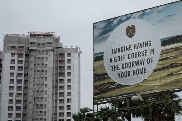 Un panneau publicitaire fait la promotion de nouveaux appartements construits près du parcours de golf olympique, en novembre 2016. (YASUYOSHI CHIBA / AFP)