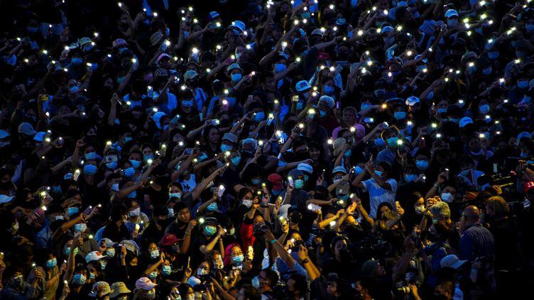 Des manifestants pro-démocratie brandissent leurs téléphones lors d'un rassemblement demandant la démission du gouvernement de Thaïlande, le 16 août 2020 à Bangkok. (ATHIT PERAWONGMETHA / REUTERS)