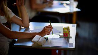 Une élève lors d'une épreuve de bac (illustration). (MARTIN BUREAU / AFP)