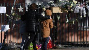Une femme et un enfant devant la mairie deSaint-Féliu-d'Avall (Pyréenées-Orientales), le 17 décembre 2017, où un rassemblement en l'hommage des victimes de la collision entre un TER et un bus scolaire a eu lieu. (PASCAL PAVANI / AFP)