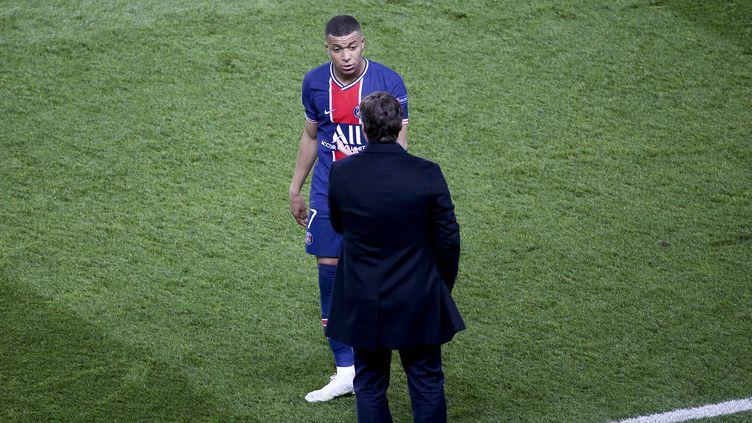 Kylian Mbappé en discussion avec son entraîneur Mauricio Pochettino, le 28 avril 2021 au Parc des Princes. (JEAN CATUFFE / AFP)