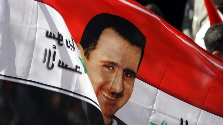 Un drapeau du président syrien Bachar Al-Assad dans une manifestation pro-régime à Damas, le 13 novembre 2011. (LOUAI BESHARA /AFP PHOTO)