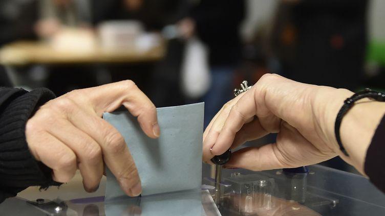 Un électeurglisse son bulletin de vote dans l'urne lors de la primaire de la gauche, le 29 janvier 2017 à Toulouse ( Haute-Garonne). (PASCAL PAVANI / AFP)