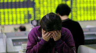 Une femme inquiétée par la chute des cours de la Bourse de Shanghaï à Nantong, dans la province du Jiangsu (Chine), le 8 juillet 2015. (XU CONGJUN / IMAGINECHINA / AFP)