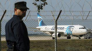 Un policier est en faction à proximité de l'aéroport de Larnaca près d'un avion de la compagnie EgyptAir détourné par des pirates, le 29 mars 2016. (YIANNIS KOURTOGLOU / REUTERS)